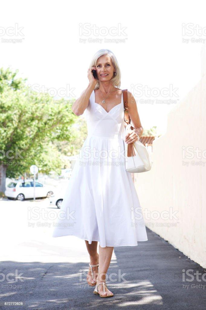 schöne ältere Frau zu Fuß auf dem Bürgersteig auf Handy – Foto