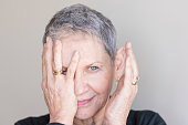 Close up portrait of beautiful older woman with short grey hair and one hand covering face against neutral background (selective focus)
