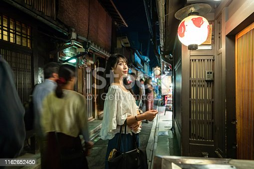 Asian female tourist enjoying traditional alley in Kyoto