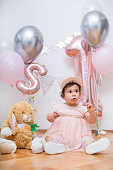 Beautiful one year old baby girl, dressed in pink, with baloons and toys celebrating her first birthday