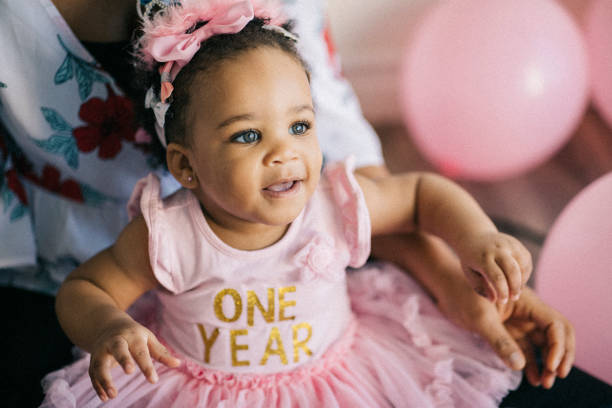 Beautiful one year old baby girl, dressed in pink, celebrating her first birthday. Beautiful people imagery. first birthday stock pictures, royalty-free photos & images