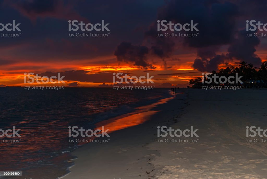Beautiful orange clouds over sunset on a beach stock photo