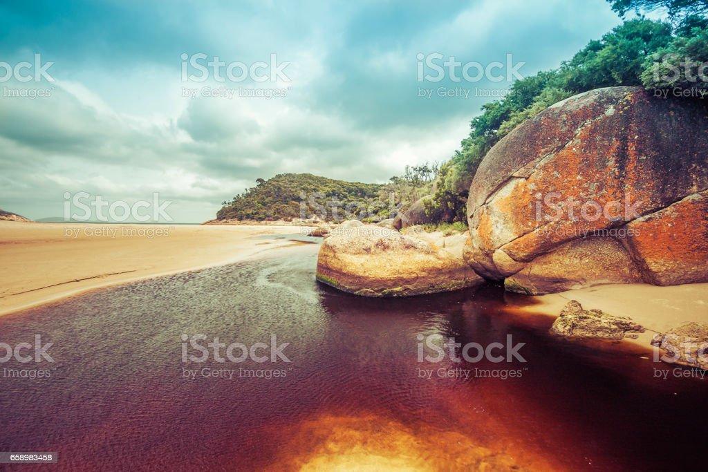 Beautiful orange rocks and brown water of Tidal River. Wilsons Promontory, Victoria, Australia stock photo