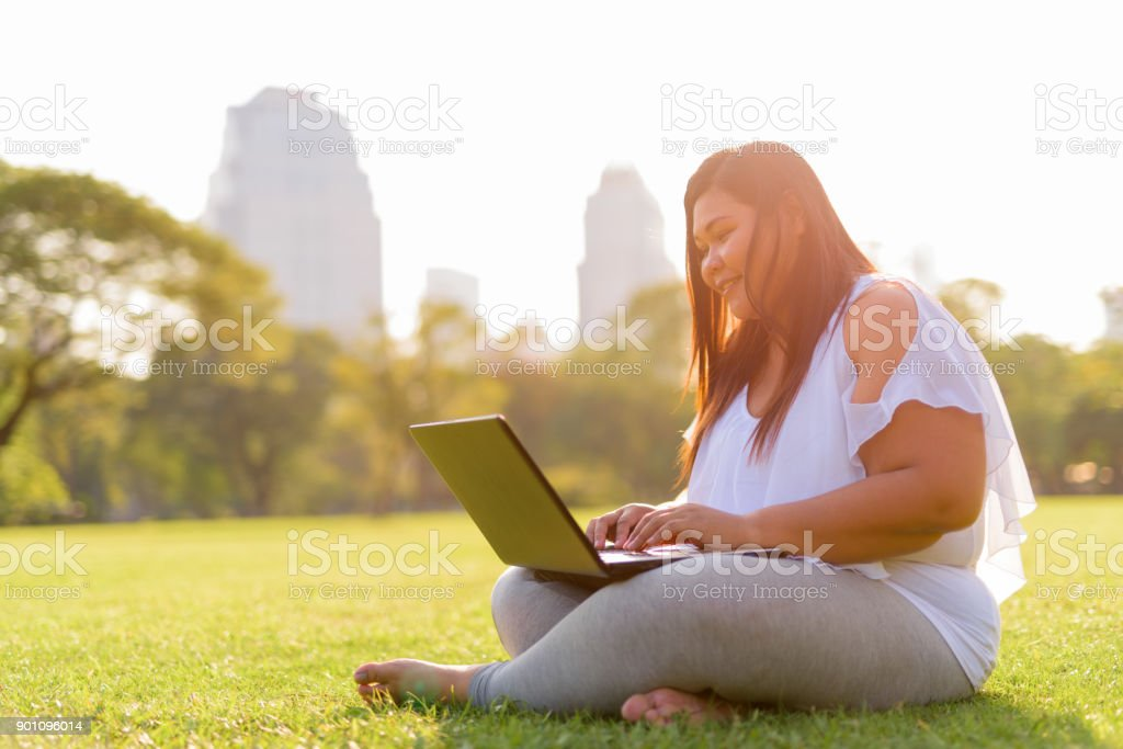Beautiful Overweight Asian Woman Using Laptop Computer In Lumpini Park stock photo