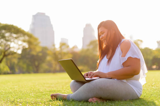 beautiful overweight asian woman using laptop computer in lumpini park - overweight stock pictures, royalty-free photos & images