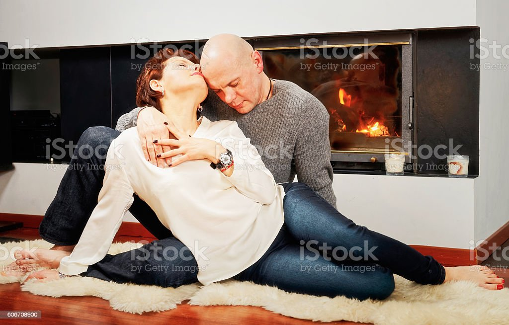 Beautiful pair sitting with passion on fur carpet near the stock photo