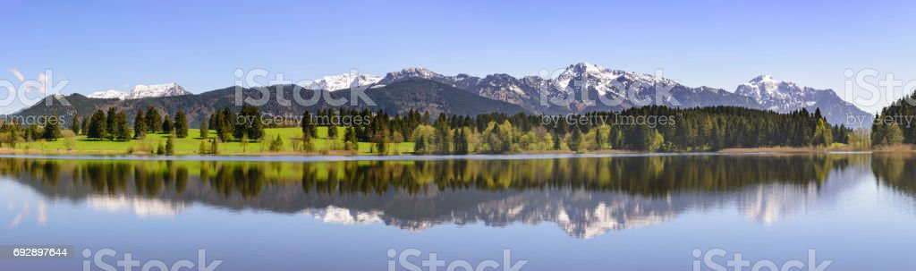 beautiful panorama landscape with alps mountains mirroring in lake stock photo