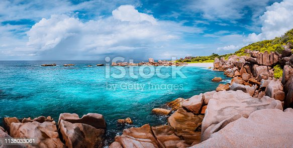 Beautiful panorama with impressive white fluffy clouds wild rocky beach Anse Marron in Seychelles. La Digue.