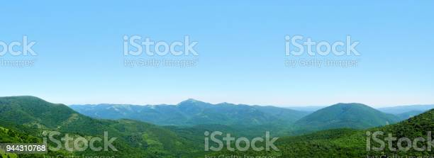 Photo of Beautiful panoramic mountain landscape, low hills and mountain peaks covered with green forest, blue sky. Skyline, Markhotsky Range, Russia