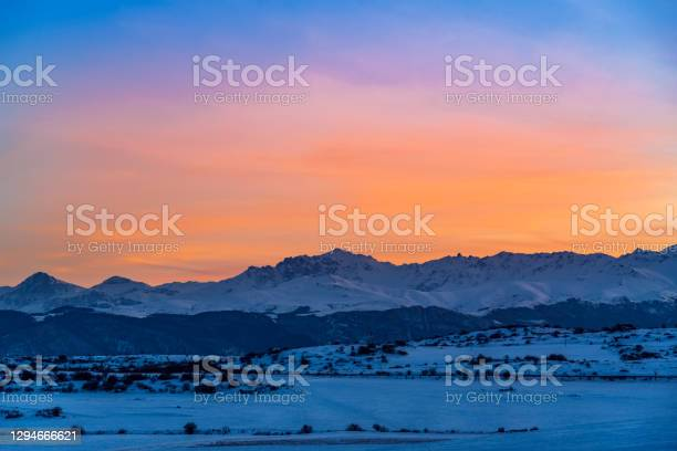 Photo of Beautiful panoramic sunset over the mountains and  snow-covered hills.