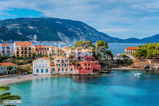 Beautiful panoramic view of Assos village with vivid colorful houses near blue turquoise colored and transparent bay lagoon. Kefalonia, Greece.