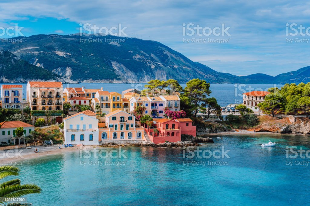 Beautiful panoramic view of Assos village with vivid colorful houses near blue turquoise colored and transparent bay lagoon. Kefalonia, Greece stock photo