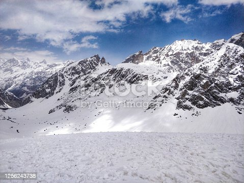 istock Beautiful panoramic view of mighty sharp peak mountains of Spiti Valley under snow in the month of June from top of high altitude Indian Himalayan pass on a Humpta pass Trek near Manali. 1256243738