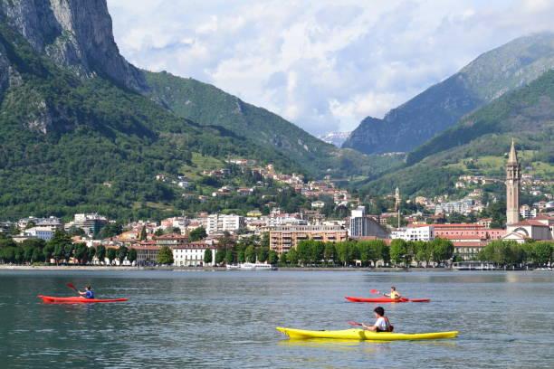 prachtig panoramisch uitzicht op de lecco lakefront in een zonnige zomerdag en kano's. - lecco lombardije stockfoto's en -beelden