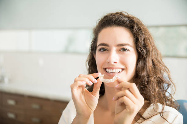 Beautiful Patient Holding Orthodontic Retainers In Dental Clinic stock photo
