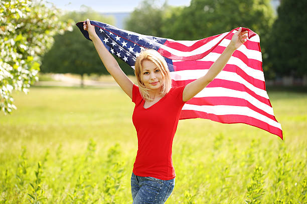 Beautiful patriotic young woman with American flag stock photo