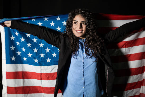 Beautiful patriotic young woman with the American flag Beautiful patriotic young woman with the American flag . Isolated on black citizenship stock pictures, royalty-free photos & images