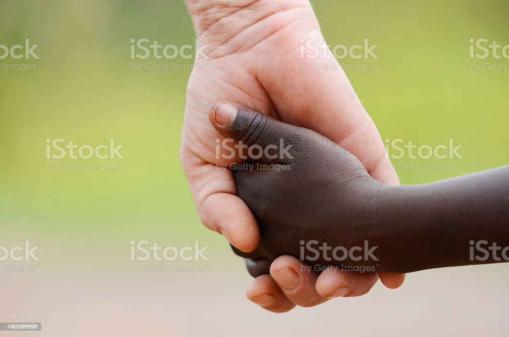 Beautiful Peace Symbol - White Woman Black Child Holding Hands stock photo