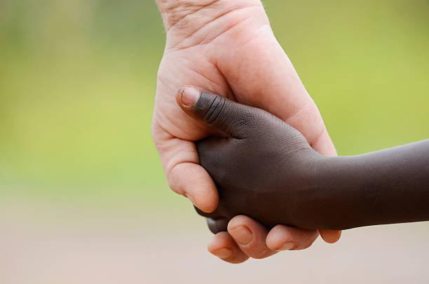 Beautiful Peace Symbol - White Woman Black Child Holding Hands stock photo