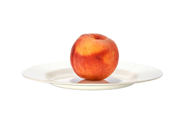 Beautiful peach on a white plate close up.