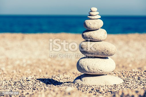 istock Beautiful pebble stack on a sandy beach 516208188
