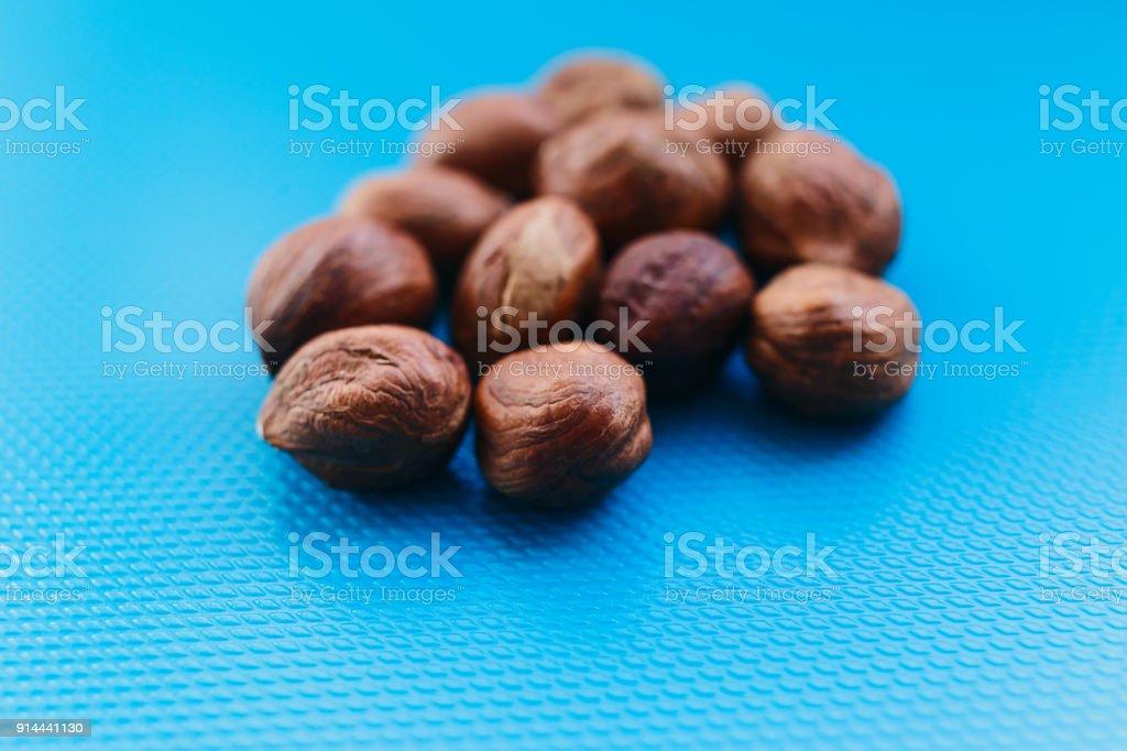 beautiful peeled hazelnuts on a blue background stock photo