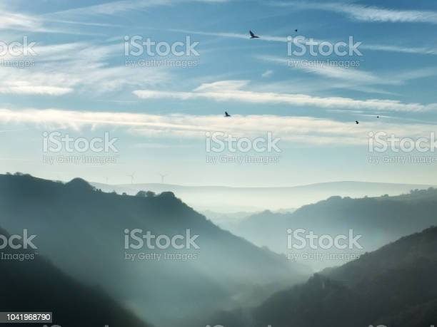 Photo of beautiful pennine landscape hills in the calder valley in west yorkshire with morning mist and fog between the hills blue sky and crows flying overhead in winter