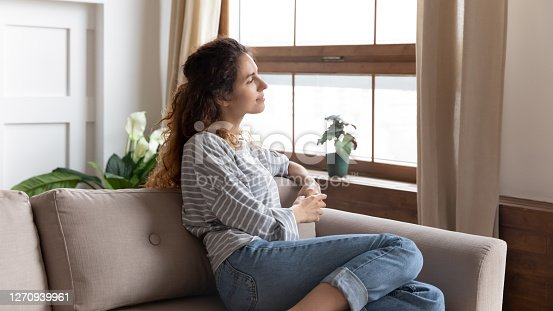 Thoughtful relaxed woman in casual clothes rest on couch in cozy modern living room looks out the window enjoy city admires view, daydreaming, smiling lost on pleasant thoughts spend weekend at home