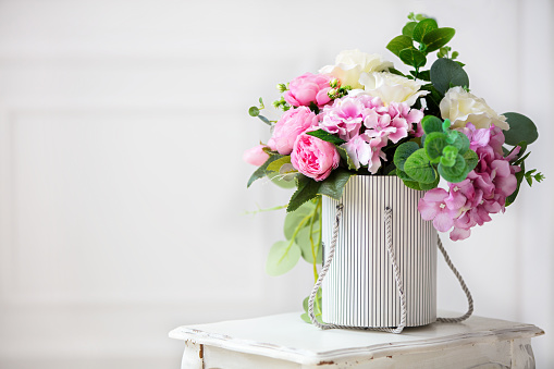 Beautiful peonies in a paper box on a white background.