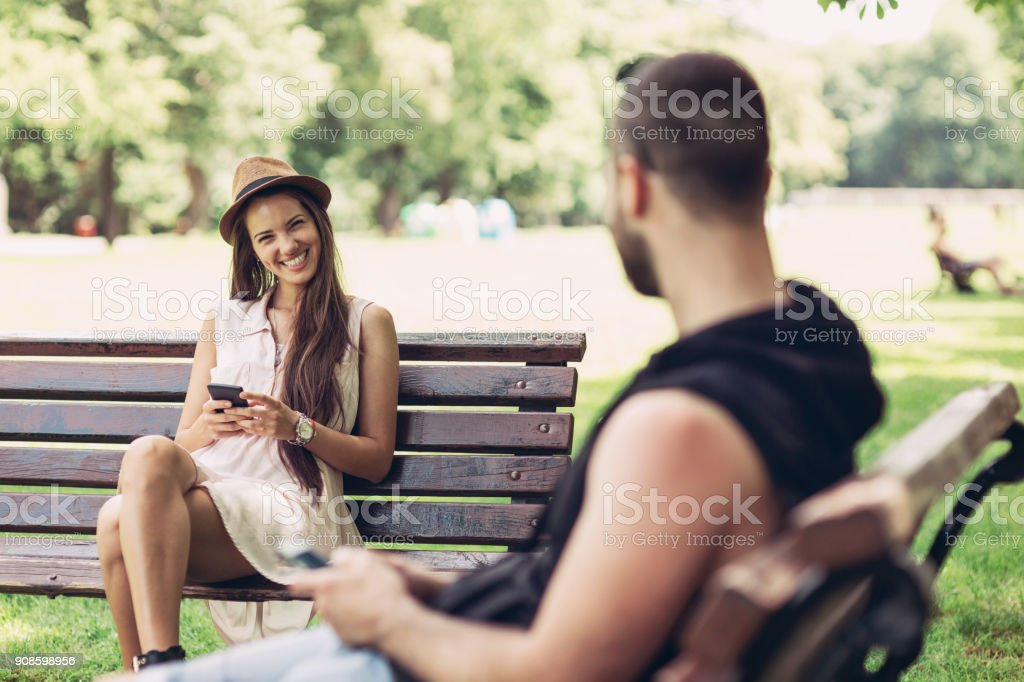 Beautiful people flirting in the park stock photo