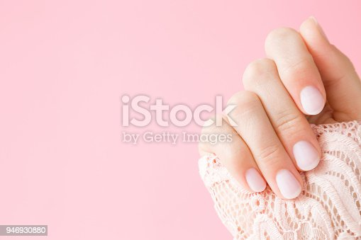 946930880istockphoto Beautiful, perfect, groomed woman's hand with light pink nails on the pastel background. Manicure, pedicure beauty salon concept. Empty place for text or logo. 946930880