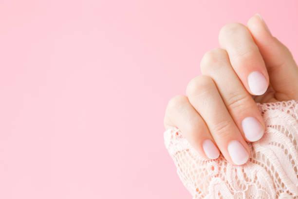 lindo, perfeito, preparado na mão de mulher com unhas rosa luz no fundo pastel. manicure, pedicure conceito de salão de beleza. lugar vazio para texto ou logotipo. - manicure - fotografias e filmes do acervo