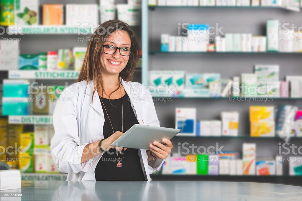 Beautiful Pharmacist with Digital Tablet in a Drugstore stock photo