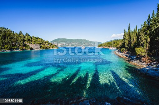istock Beautiful Phoki Beach surrounded by cypress trees in the evening sunlight. Amazing seascape of Ionian Sea. Cypress shadows on the clear azure water. Greece 1016301446