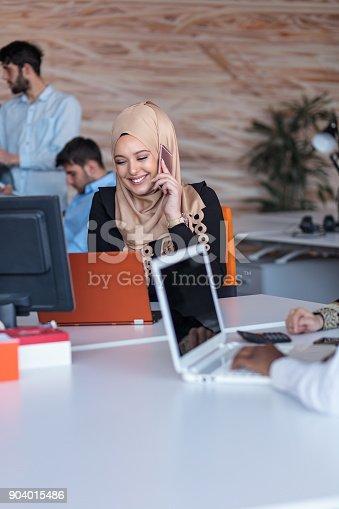 istock Beautiful phone operator Arab woman working in modern startup office 904015486