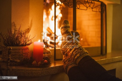 Beautiful photo of a unrecognizable man that is warming his feet on the fireplace wearing Christmas  socks