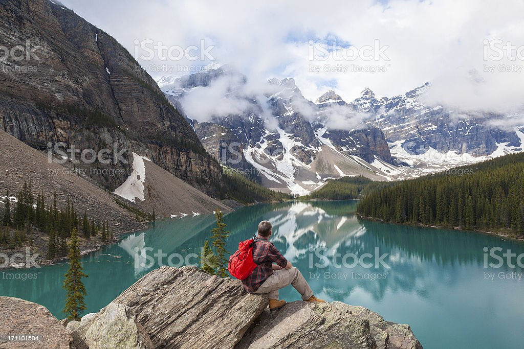 Beautiful photo of a man atop rocks looking at Moraine lake stock photo