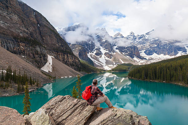 Beautiful photo of a man atop rocks looking at Moraine lake Hiking man sitting down with rucksack backpack standing on tree log by Moraine Lake looking at snow covered Rocky Mountain peaks, Banff National Park, Alberta Canada moraine lake stock pictures, royalty-free photos & images