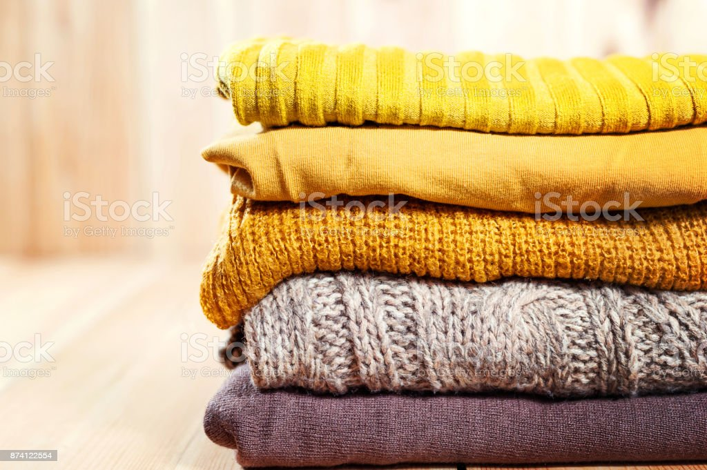 Beautiful photo of a pile of knitted yellow woman sweaters. Woman fashion. Autumn clothing. stock photo