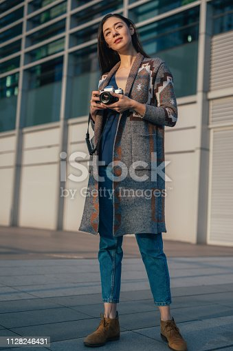 One beautiful female photographer in casual clothing standing outdoors and holding digital camera.