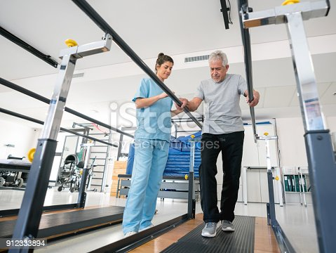 Beautiful physiotherapist helping a senior patient on his recovery walking between parallel bars both looking very happy and smiling