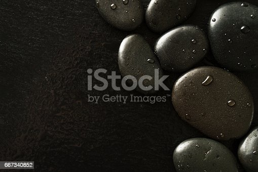 istock Beautiful picture of Spa Hot Stones, View from Above. Dark Background. Top. Spa Concept. Side Composition. 667340852