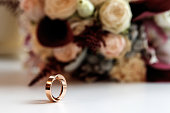 A beautiful picture with wedding rings lies against the background of a bouquet of flowers