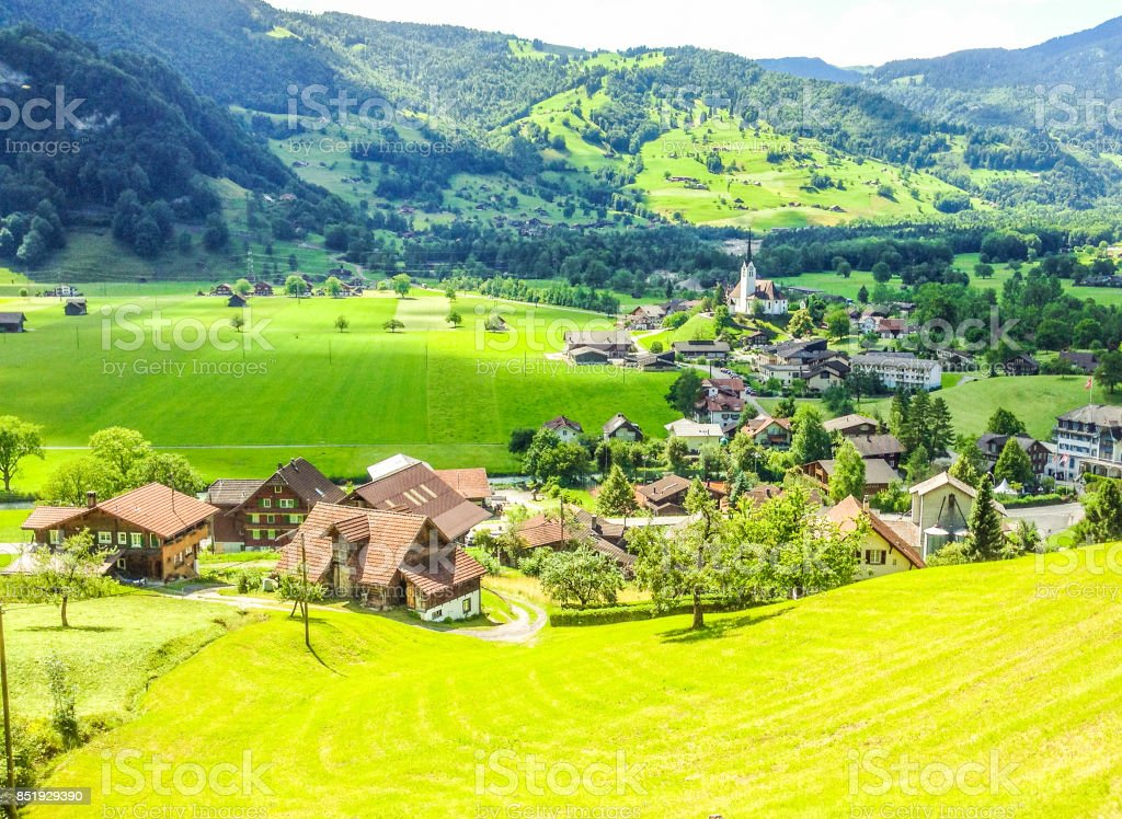 Beautiful, picturesque, stunning summer day view of Lungern Village surrounding its Pfarrkirche  Catholic Church from the train window, Obwalden Canton, Switzerland, Europe. stock photo