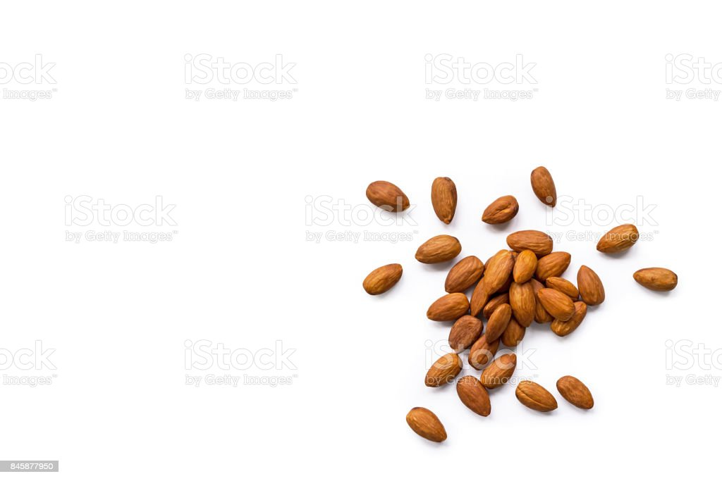 beautiful pile of roasted organic almonds with the peel isolated on a white background. royalty-free stock photo