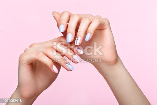 istock Beautiful pink and blue manicure with crystals on female hand. Close-up. 1004052418