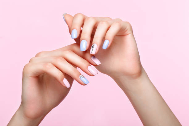 Beautiful pink and blue manicure with crystals on female hand. Close-up. stock photo