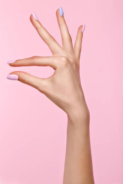 schöne rosa und blauen maniküre mit kristallen auf der weiblichen seite. close-up. - nägel lackieren stock-fotos und bilder