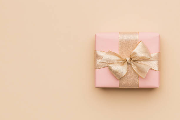 beautiful pink christmas gift with golden ribbon isolated on beige paper background. christmas present background with copy space. - beige background stock photos and pictures