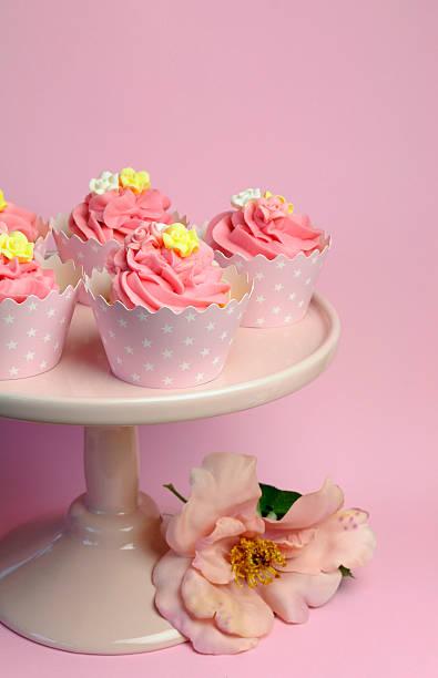 schöne rosa dekoriert cupcakes auf stand-vertikal. - brautparty kuchen stock-fotos und bilder